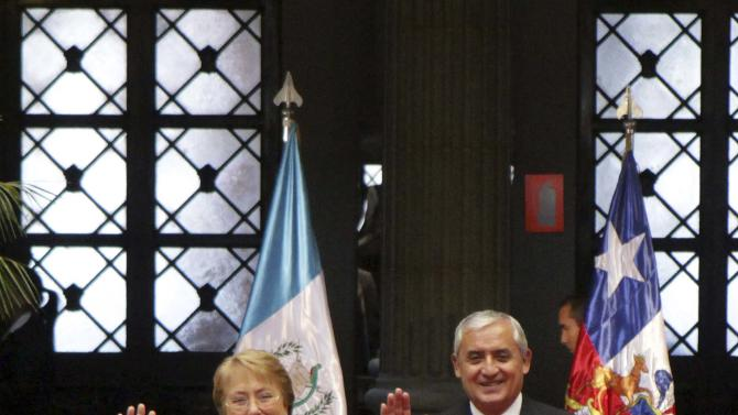 Chile's President Bachelet waves next to Guatemala's President Otto Perez during a welcoming ceremony in the presidential palace in Guatemala City