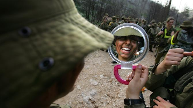 FILE - In this Feb. 20, 2007 file photo, an Israeli soldier laughs as she looks in a mirror during a military training session near Jerusalem. Israel, Canada, France, Norway, Australia, New Zealand and in 2013, the U.S. have opened their fighting ranks to female soldiers. (AP Photo/Oded Balilty)
