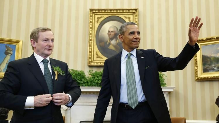 U.S. President Obama waves next to Irish PM Kenny in the Oval Office of the White House in Washington