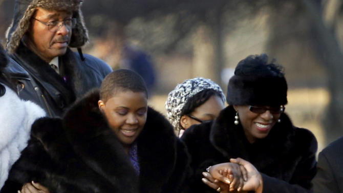 Cleopatra Pendleton, left, is escorted to the gravesite of her daughter Hadiya Pendleton during funeral services at the Cedar Park Cemetery, Saturday, Feb. 9, 2013, in Calumet Park, Ill. Pendleton was killed on Jan. 29, when a gunman opened fire on her and some friends seeking shelter in a park from the rain about a mile from President Obama's Chicago home. First lady Michelle Obama attended the funeral with Senior White House Adviser Valerie Jarrett and Secretary of Education Arne Duncan. (AP Photo/Charles Rex Arbogast)