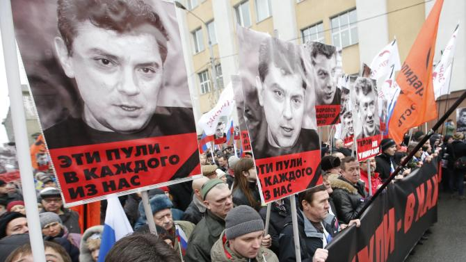 People holds posters during march to commemorate Kremlin critic Nemtsov in central Moscow