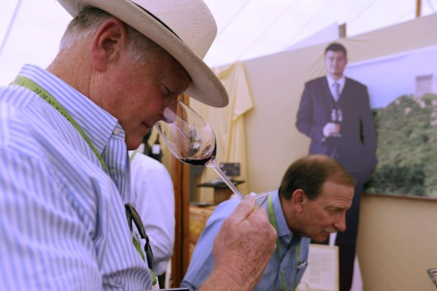 In this photo taken Friday May 31, 2013, Tom Davies samples a Yao Ming Family Cabernet Sauvingon wine during Auction Napa Valley at Rutherford Vineyard in St. Helena, Calif. Forget the tie. Think besp