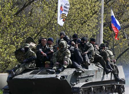 Armed men drive an armoured personnel carrier with a Russian flag seen on the top in Slaviansk