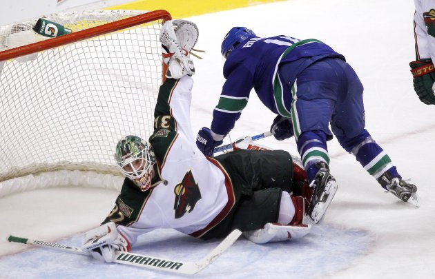 Minnesota Wild goaltender Niklas Backstrom makes a save while Vancouver Canucks Alex Burrows falls onto him during third period NHL game in Vancouver