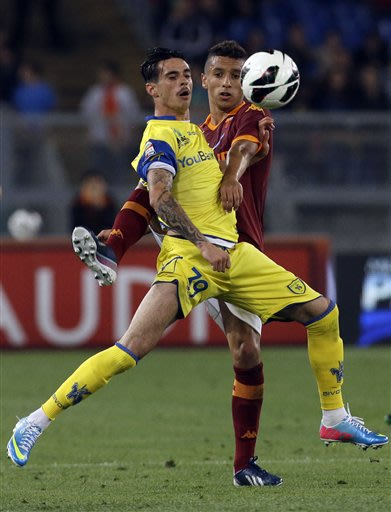 AS Roma's Marquinhos, of Brazil, right, and Chievo's Adrian Stoian, of Romania, fight for the ball during a Serie A soccer match between AS Roma and Chievo in Rome, Tuesday, May 7, 2013