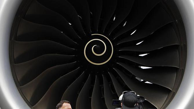 Journalists work next to the Rolls Royce engine of an Airbus A350 on display at the Singapore Airshow
