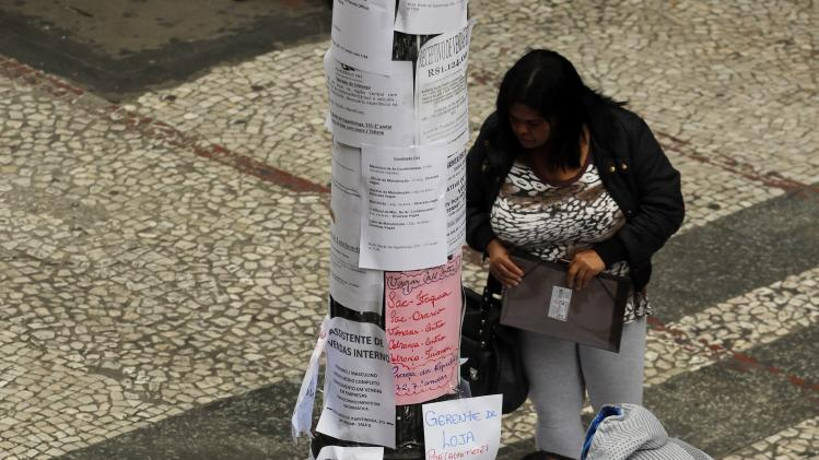 People look at a list of job offers posted in a main street in downtown Sao Paulo