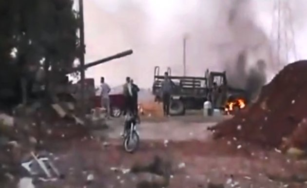 This image made from amateur video released by the Ugarit News and accessed Monday, July 30, 2012, purports to show Free Syrian Army soldiers in Anadan 16 kilometers (10 miles), from Aleppo, Syria. Syrian government forces mounted new ground attacks against rebel-controlled neighborhoods in Syria's commercial hub of Aleppo, the state media said Monday, July 30, but failed to dislodge the opposition from their strongholds, according to activists. (AP Photo/Ugarit News via AP video) THE ASSOCIATED PRESS IS UNABLE TO INDEPENDENTLY VERIFY THE AUTHENTICITY, CONTENT, LOCATION OR DATE OF THIS HANDOUT PHOTO