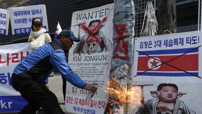 A South Korean protester burns banners with pictures of North Korean leader Kim Jong Un during an anti-North Korea protest rally in downtown Seoul, South Korea Thursday, April 18, 2013. North Korea would collapse without support from its economic benefactor China, U.S. Secretary of State John Kerry, who was on East Asian tour last week, said Wednesday, stressing the importance of working with Beijing to address North Korean threats and its nuclear program. (AP Photo/Kin Cheung)