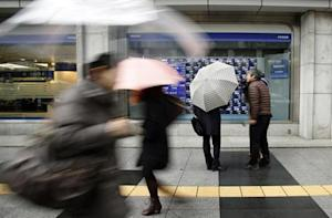 A media crew conducts an interview to a pedestrian as he looks at an electronic board showing stock prices outside a brokerage in Tokyo February 4, 2014. REUTERS/Yuya Shino
