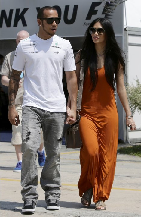 Mercedes Formula One driver Hamilton walks with girlfriend Scherzinger in the paddock before the start of the third practice session of the Malaysian F1 Grand Prix at Sepang International Circuit outs