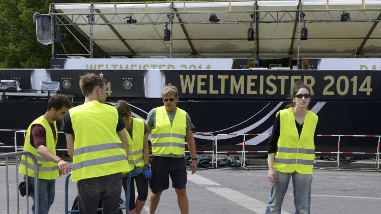 Workers pass a security fence at a public viewing area during preparations for the arrival of Germany's national soccer team, in Berlin