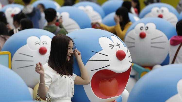A visitor poses for a photo next to a Doraemon model during an exhibition in Beijing