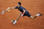 Serbia&#39;s Novak Djokovic stretches to make a return to Rafael Nadal during the French Open men&#39;s singles final at Roland Garros stadium in Paris on June 10. Nadal took the first two sets 6-4, 6-3 before Djokovic fought back to win the third 6-2 on a rain-affedted day