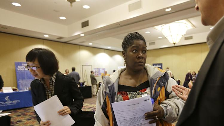 In this Thursday, Oct. 25, 2012, photo, Angela Winters of Schenectady, N.Y., center, talks to a recruiter during a job fair at the Marriott Hotel on ,in Colonie, N.Y. The number of people seeking U.S. unemployment aid remained elevated for a second straight week because Superstorm Sandy forced many people to seek temporary benefits. The Labor Department said Wednesday, Nov. 21, 2012,  that first-time applications for benefits fell by 41,000 last week to a seasonally adjusted 410,000. That offset only part of the previous week's surge.(AP Photo/Mike Groll)