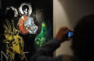 "<p>A visitor takes a picture of a painting at the ""Spiritual Abuse"" painting exhibition at the Winzavod Art Gallery in Moscow. The exhibition, by the artist Evgenia Maltseva, includes around 10 paintings, some of them styled on religious icons and others featuring hooded faces reminiscent of Pussy Riot members.</p>"