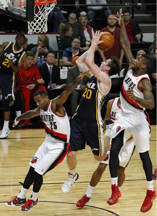 Utah Jazz small forward Gordon Hayward (20) shoots between Portland Trail Blazers point guard Mo Williams (25)  and Portland Trail Blazers power forward Thomas Robinson (41) in the second half of a pr