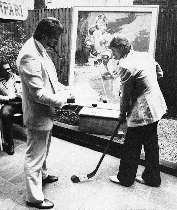 FILE - In this May 14, 1981 file photo, artist LeRoy Neiman, standing left, sketches Edmonton Oilers star forward Wayne Gretzky , right, at a restaurant in New York following the unveiling of Neiman's