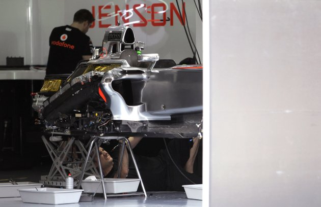 McLaren F1 crew work on Jenson Button's car at the Sepang International Circuit, ahead of the Malaysian F1 Grand Prix