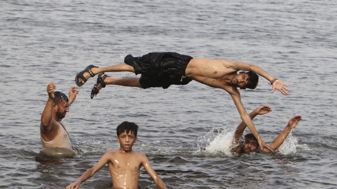 People cool themselves off in a water during a hot weather in Karachi, Pakistan, Wednesday, July 1, 2015. More than 1,200 people lost their lives due to a weeklong heat wave in the southern port city of Karachi, suffering from heatstroke and dehydration. (AP Photo/Fareed Khan)