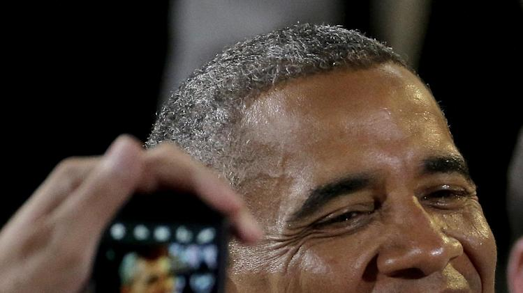 A guest uses their cellphone to photograph President Barack Obama as greets the crowd after speaking about the economy, Wednesday, July 30, 2014, at the Uptown Theater in Kansas City, Mo. (AP Photo/Charlie Riedel)