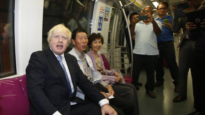 Mayor of London Johnson sits next to two Japanese tourists on the subway train during his visit in Singapore