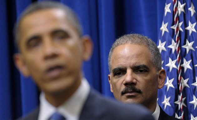 FILE - In this Feb. 9, 2012 file photo, Attorney General Eric holder listens at right as President Barack Obama speaks about a mortgage settlement in the Eisenhower Executive Office building on the Wh