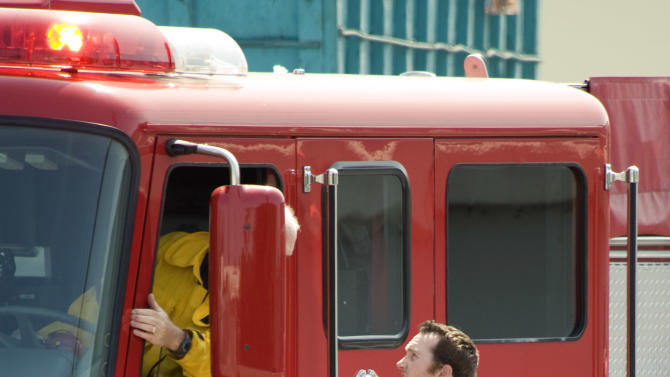 Bee Keeper Technician Kris Fricke gets briefed from Santa Ana firefighters on a swarm of aggressive honey bees in Santa Ana, Calif. on  Thursday, Sept. 15, 2011.  (AP Photo/Orange County Register, Ken Steinhardt)