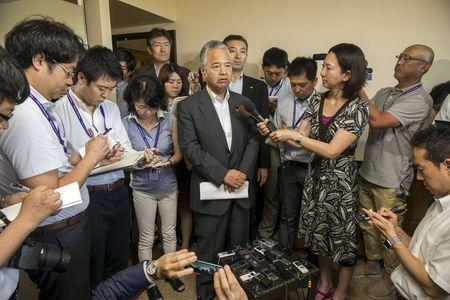Japan's Economy Minister Akira Amari speaks at a news conference surrounded by Japanese press, at the Westin Resort in Lahaina, Maui, Hawaii