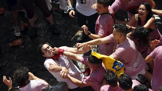A reveller is punched in the face by another reveller during the start of the San Fermin Festival in Pamplona
