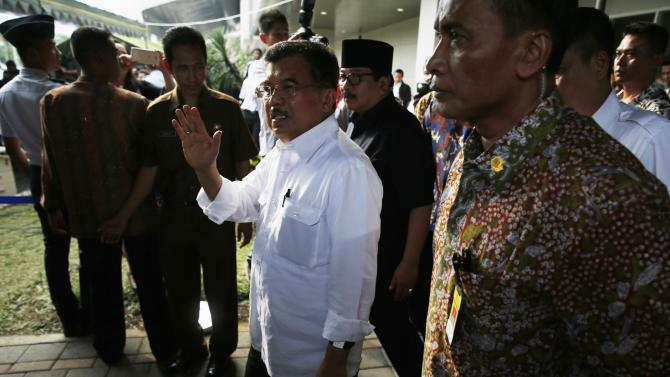 Indonesia's Vice President Kalla waves as he walks to meet the family members of passengers onboard AirAsia flight QZ8501 at a waiting area in Juanda International Airport