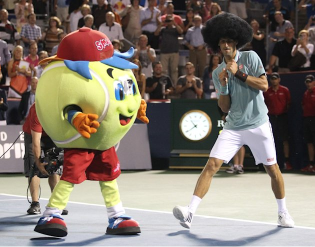 Novak Djokovic of Serbia dons a wig and dances following his win over Denis Istomin of Uzbekistan in Montreal