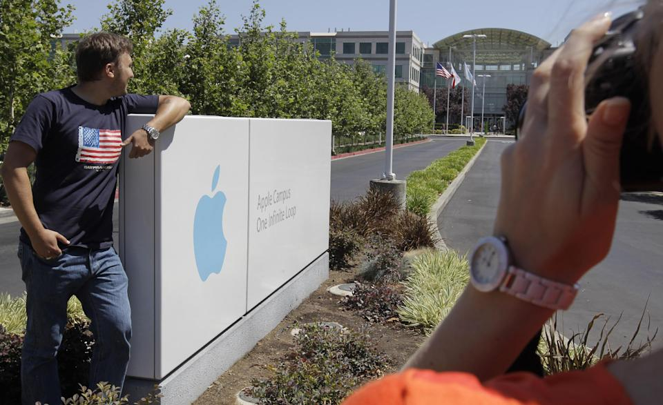 Russian tourists pose outside of Apple headquarters in Cupertino, Calif., Monday, Aug. 20, 2012.  On Monday, Apple became the most valuable company ever, with a market value of $623 billion, surpassing Microsoft's record from 1999.(AP Photo/Paul Sakuma)
