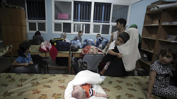 Displaced Palestinians seek refuge in a United Nations school in Gaza City after fleeing their homes Sunday, July 13, 2014. Israel has called on residents of the northern Gaza Strip to evacuate their homes, suggesting a coming attack after its troops earlier launched a brief raid. (AP Photo/Khalil Hamra)