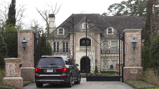 A car enters a gate to the home of NFL running back Adrian Peterson Wednesday, March 4, 2015, near Houston. Minnesota Vikings head coach Mike Zimmer and GM Rick Spielman plan to travel to Peterson's home near Houston on Wednesday to meet with their disgruntled star running back, a person with knowledge of the situation told The Associated Press. The person requested anonymity because neither side was publicly discussing the process. (AP Photo/ The Courier, Jason Fochtman)