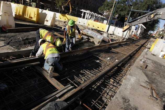 In this Nov. 8, 2012 photo, workers continue work on street car track construction on Loyola Avenue in New Orleans. With the NFL football Super Bowl less than three months away, New Orleans is rushing to lay streetcar tracks through one of its busiest corridors to connect by trolley the Louisiana Superdome, where the big game will be played Feb. 3, and the French Quarter. At the same time, developers view the new streetcar as crucial in plans to spark a downtown renaissance where one of the city's most vibrant jazz districts has been replaced by parking lots and high rise buildings. (AP Photo/Gerald Herbert)