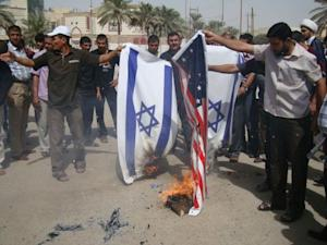 Iraqi supporters of Shiite cleric Moqtada al-Sadr's movement burn the Israeli and the US flags during a protest in Kut