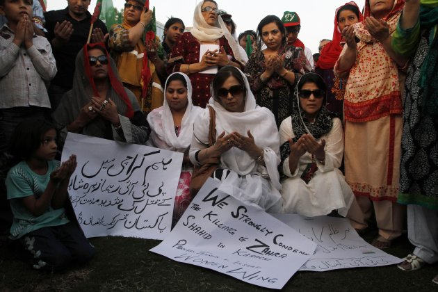 Supporters of Pakistan Tehreek-e-Insaf pray during a protest against the killing of Zara Shahid Hussain, a leading member of the PTI, in Lahore