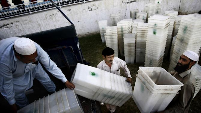 Pakistan Election Commission staff load ballot boxes on a truck en-route to polling stations in Peshawar, Pakistan, Thursday, May 9, 2013. Pakistan is scheduled to hold parliamentary elections on May 11, the first transition between democratically elected governments in a country that has experienced three military coups and constant political instability since its creation in 1947. (AP Photo/Mohammad Sajjad)