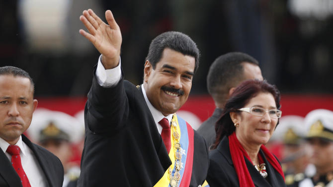 Venezuela's President Nicolas Maduro waves from a vehicle, next to his companion Cilia Flores, during a military ceremony recognizing him as Commander-in-chief to the military at the Paseo Los  Proceres in Caracas, Venezuela, Friday, April, 19, 2013. Maduro, who has the support of the Chavista bases, needs all the momentum he can muster to consolidate control of a country struggling with shortages of food and medicines; chronic power outages; one of the world's highest homicide and kidnapping rates. (AP Photo/Ariana Cubillos)