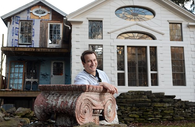 "In this photo taken Feb. 1, 2012, Bronson Pinchot poses for photos near the rear facade of the Decker House, one of six properties he owns in Harford, Pa. Pinchot, best known for his starring role on the 1980's sitcom ""Perfect Strangers,"" is back on TV with a new show about restoring his historic Pennsylvania homes. The show, ""The Bronson Pinchot Project,"" premiered this month on the DIY cable network. (AP Photo/Heather Ainsworth)"