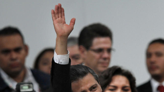 Mexico's President Enrique Pena Nieto waves during a national convention of the Institutional Revolutionary Party (PRI), in Mexico City, Sunday,  March 3, 2013. Mexico's ruling party changed on Sunday its platform to allow a reform that could bring private investment into the state-owned oil monopoly, in a country where oil is a source of national pride. (AP Photo/Marco Ugarte)