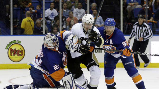 New York Islanders center John Tavares (91) and goalie Evgeni Nabokov (20), of Kazakhstan, put the squeeze on Pittsburgh Penguins center Evgeni Malkin (71), also of Russia, in the third period of Game 6 of their first-round NHL Stanley Cup playoff hockey series in Uniondale, N.Y., Saturday, May 11, 2013. (AP Photo/Kathy Willens)