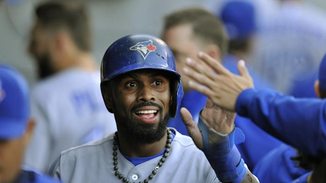 Toronto Blue Jays' Jose Reyes (7), celebrates with teammates in the dugout after scoring on a Jose Bautista groundout during the first inning of a baseball game against the Chicago White Sox Tuesday, July 7, 2015 in Chicago. (AP Photo/Paul Beaty)