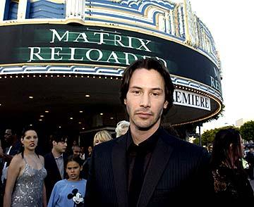 Keanu Reeves tries to ignore the angry remarks from the little girl behind him, whom he has just informed that there is no Santa Claus, at the Hollywood premiere of Warner Brothers' The Matrix: Reloaded