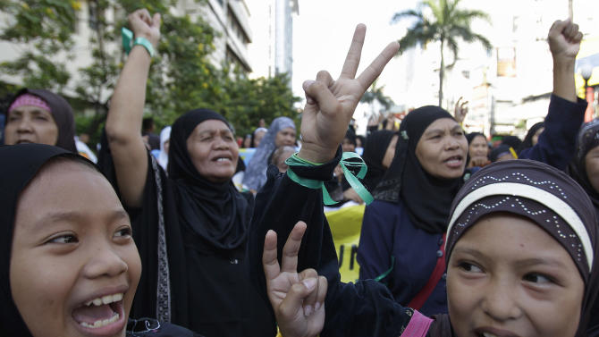 Filipino Muslim girls flash the peace sign during a rally in support of a preliminary peace agreement between the government and the nation's largest Muslim rebel group outside the Malacanang presidential palace in Manila, Philippines, on Sunday Oct. 14, 2012. About 200 Muslim rebels led by their elusive chief arrived in the Philippine capital on Sunday for the signing of a preliminary peace pact aimed at ending one of Asia's longest-running insurgencies. (AP Photo/Aaron Favila)