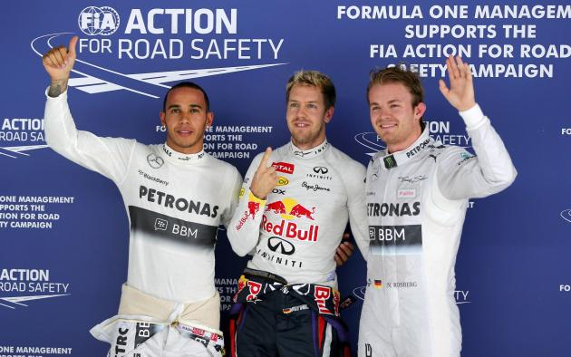 Mercedes Formula One driver Hamilton, Red Bull Formula One driver Vettel and Mercedes Formula One driver Rosberg pose after the qualifying session of the Indian F1 Grand Prix at the Buddh Internationa
