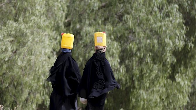 Women carry jerrycans they filled with water from a public tap amid an acute shortage of water supply to houses in Sanaa