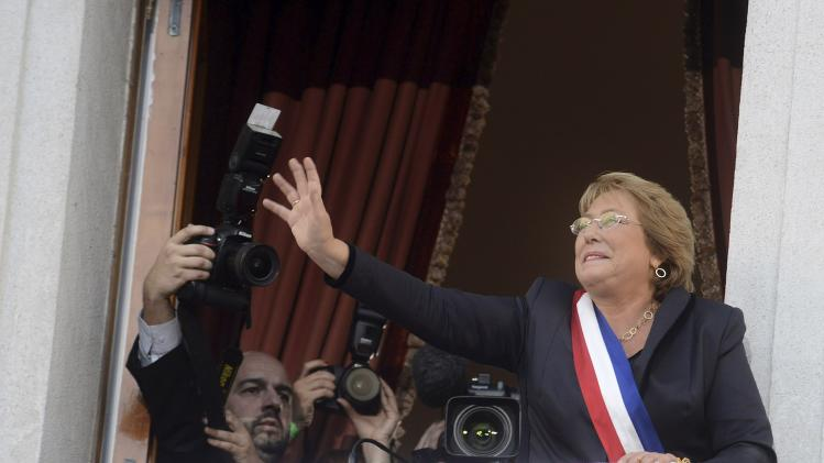 Chile's President Michelle Bachelet waves at supporters from the balcony of the La Moneda Presidential Palace in Santiago