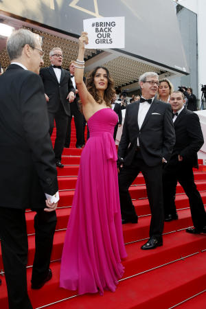 """Actress Salma Hayek holds up a sign reading """"bring back our girls"""", part of a campaign calling for the release of nearly 300 abducted Nigerian schoolgirls being held by Nigerian Islamic extremist group Boko Haram, as she arrives for the screening of Saint-Laurent at the 67th international film festival, Cannes, southern France, Saturday, May 17, 2014.(AP Photo/Alastair Grant)"""